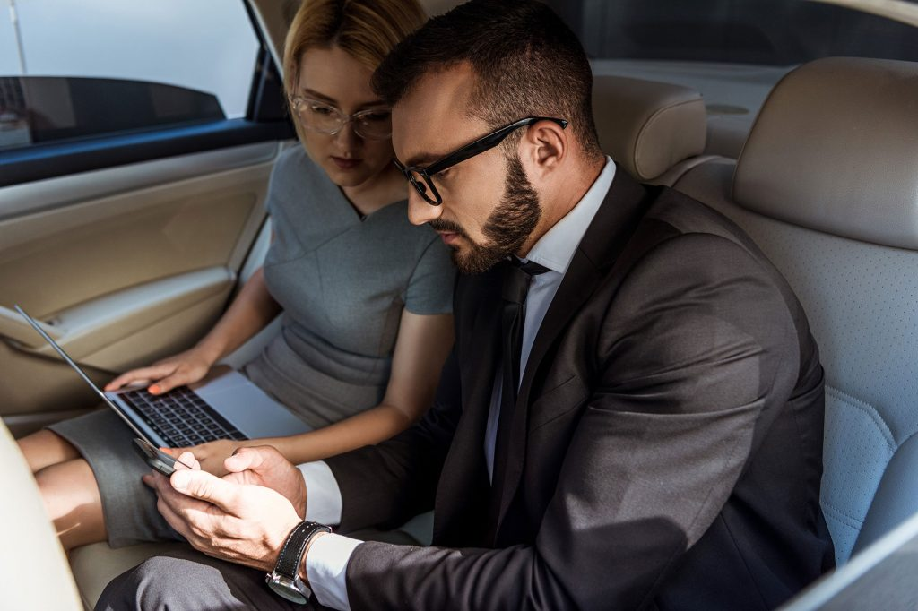 businessman showing phone - working in car - businesswoman holding a laptop